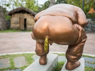 Срущий памятник с золотой какашкой.
